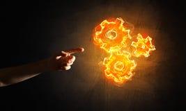 Konzept von Teamworking oder von Organisation stellte sich durch Hände in glühenden Zahnrädern der Note und des Feuers dar Stockbilder