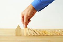 Konzeptbild der Immobilienversicherung und -schutzes bemannen Sie die Hände, die den Domino-Effekt blockieren und ein kleines Hau Lizenzfreies Stockfoto