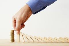 Konzeptbild der Investierung und des Ein Bankkonto habens bemannen Sie die Hände, die den Domino-Effekt blockieren und einen Stap Lizenzfreies Stockbild
