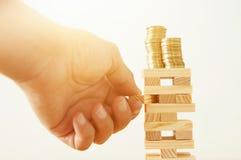 Konzeptbild der Investierung und des Ein Bankkonto habens bemannen Sie die Hände, die den Domino-Effekt blockieren und einen Stap Stockfotografie