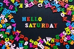 Konzeptdesign - das Wort HALLO SAMSTAG von den mehrfarbigen hölzernen Buchstaben auf einem schwarzen Hintergrund, kreative Idee lizenzfreies stockbild