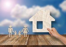Konzepte der Hand setzten Haus und Familie auf hölzerne Tabelle Lizenzfreies Stockbild