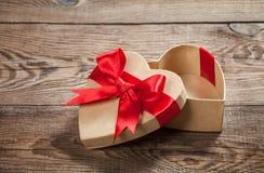 Konzeptgeschenk Kasten in Form von Herzen auf den alten Brettern stockbild