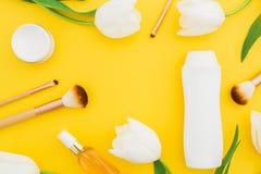 Konzepthintergrund mit Shampooflasche, Parfüm, Creme und weißen Tulpen blüht auf gelbem Hintergrund Schönheitszusammensetzung Fla Lizenzfreies Stockfoto