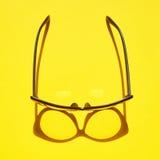 Konzepthintergrund von den schwarzen Gläsern, die über das gelbe SP schwimmen Lizenzfreies Stockfoto