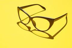 Konzepthintergrund von den schwarzen Gläsern, die über das gelbe SP schwimmen Lizenzfreie Stockfotografie