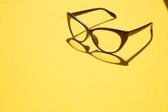 Konzepthintergrund von den schwarzen Gläsern, die über das gelbe SP schwimmen Lizenzfreie Stockfotos