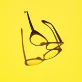 Konzepthintergrund von den schwarzen Gläsern, die über das gelbe SP schwimmen Stockfoto