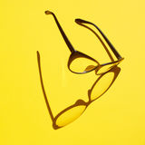 Konzepthintergrund von den schwarzen Gläsern, die über das gelbe SP schwimmen Stockfotos