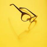 Konzepthintergrund von den schwarzen Gläsern, die über das gelbe SP schwimmen Stockbild