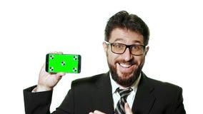 Konzeptmodell Bärtiger Geschäftsmann mit den Gläsern, die einen grünen Schirm Smartphone halten stock footage