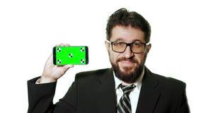 Konzeptmodell Bärtiger Geschäftsmann mit den Gläsern, die einen grünen Schirm Smartphone halten stock video