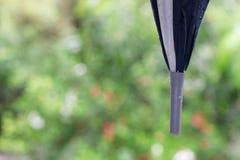 Konzeptregenschirm mit Regen lässt das Halten in der Regenzeit sich schützen fallen stockfoto