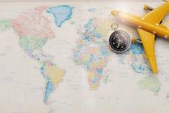 Konzeptreisetourismus, Flugzeugmodelle und Kompass gesetzt auf die Weltplatte lizenzfreies stockbild