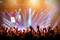 Konzertsaal mit einem hellen Stadium und Leuteschattenbilder während eines Konzerts stockfotos