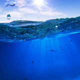 Konzipieren Sie Schablone mit Unterwasserteil und Sonnenuntergangoberlicht splitte Stockbilder