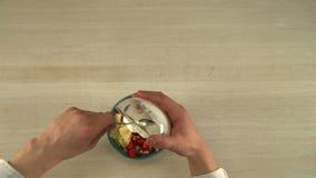 Kooktoestel gietende zure room in fruitsaladevideo stock videobeelden