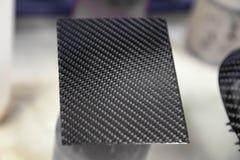 Koolstofplaat grijs en zwart in de vorm van het weven van Kevlar, een zeer duurzaam en lichtgewicht modern materiaal voor de prod royalty-vrije stock fotografie