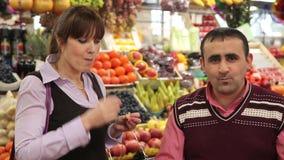 Koop bij de landbouwbedrijfmarkt De verkoper helpt de vrouw stock videobeelden