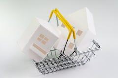 Koop en verkoop huis, de bezitsvraag en levering of onroerende goederen het kopen concept, kleine het winkelen mand met hoogtepun royalty-vrije stock foto