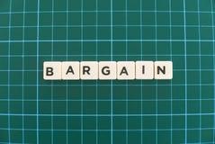 Koopjeswoord van vierkant brievenwoord wordt gemaakt op groene vierkante matachtergrond die royalty-vrije stock afbeeldingen