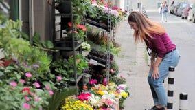 Koopt het jonge meisje van Nice verse bloemen in een straatwinkel stock video