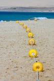 Koord van gele tellersboeien op zandig strand royalty-vrije stock foto's
