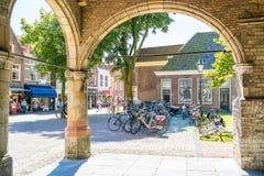 Koorstraat shops, people and arcades of church in Alkmaar, Nethe Royalty Free Stock Image