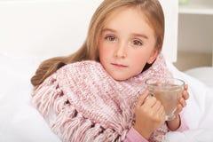 Koorts, koude en griep - Geneesmiddelen en hete thee in dichtbijgelegen, ziek meisje i royalty-vrije stock fotografie
