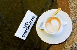 Kop cappuccino's op no-smoking lijst stock afbeelding