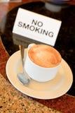 Kop cappuccino's op no-smoking lijst royalty-vrije stock foto's