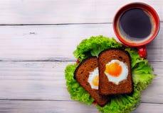 Kop coffe en twee gebraden eieren in toost op de salade Hoogste mening Stock Afbeeldingen