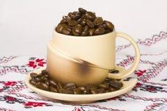 Kop die met koffiebonen wordt gevuld Royalty-vrije Stock Foto's