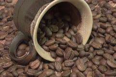 Kop die met koffiebonen wordt gevuld Royalty-vrije Stock Afbeeldingen