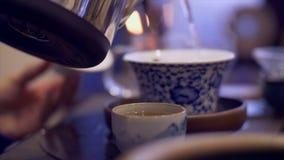 Kop die van hete thee zich op lijst bevinden Mannelijk hand gietend warm water voor het brouwen van thee stock footage