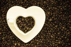 Kop en schotel op de achtergrond van koffiebonen Royalty-vrije Stock Fotografie