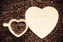 Kop en schotel op de achtergrond van koffiebonen Stock Foto