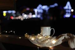 Kop hete drank, sweater en Kerstmislichten op houten traliewerk in openlucht tegen vage achtergrond, ruimte voor tekst royalty-vrije stock afbeelding
