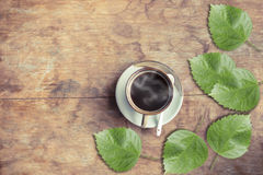 Kop hete koffie en groene bladeren op oude houten lijst De koffie heeft het knippen weg Stock Fotografie
