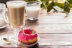 Kop hete koffie latte dranken met verglaasde doughnut Stock Afbeelding