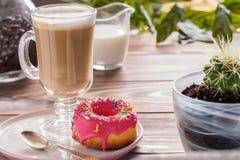 Kop hete koffie latte dranken met verglaasde doughnut Stock Afbeeldingen