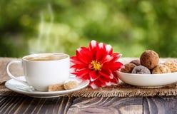 Kop koffie, bloemen en snoepjes shekoladnye op een houten tabl Royalty-vrije Stock Fotografie