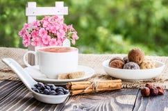 Kop koffie, bloemen en snoepjes shekoladnye op een houten tabl Royalty-vrije Stock Afbeelding
