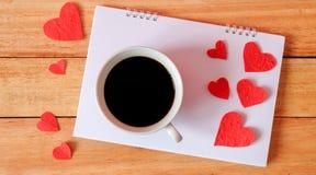 Kop koffie en harten op een houten achtergrond De koffie calen  Stock Afbeeldingen