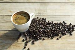 Kop koffie en koffiebonen op houten achtergrond stock fotografie