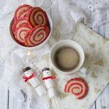Kop koffie met een heemstsneeuwman en koekjes in de vorm van een spiraal in de Kerstmislijst Comfortabel de winterontbijt Nieuwe  stock afbeelding