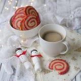 Kop koffie met een heemstsneeuwman en koekjes in de vorm van een spiraal in de Kerstmislijst Comfortabel de winterontbijt Nieuwe  stock fotografie