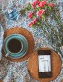 Kop koffie, mobiele telefoon met Goedemorgenbericht en roze anjers op bloemenachtergrond royalty-vrije stock foto