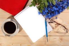 Kop koffie, notitieboekje, pen, bril en korenbloemen Royalty-vrije Stock Afbeeldingen
