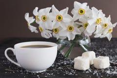 Kop koffie, Rahat-lokum met kokosnoot en narcissen op zwart w royalty-vrije stock fotografie
